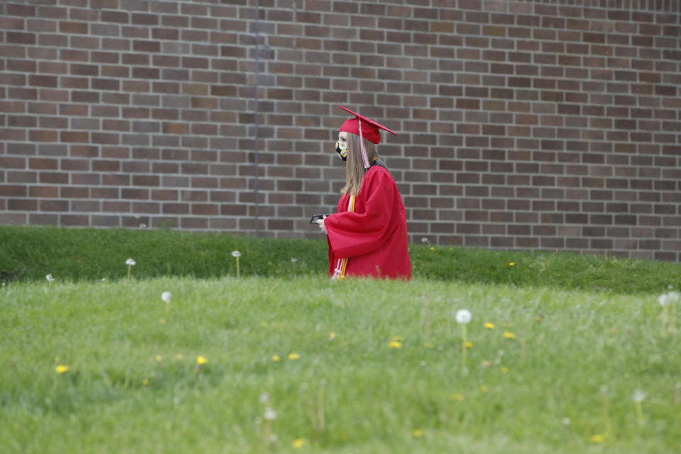 """A graduate student arrives to pick up her diploma at Bradley-Bourbonnais Community High School on May 6, 2020 in Bradley, Illinois. - A speech by Barack Obama, a photo finish at Daytona, or a wild, livestreamed party in the family living room? Americans are dreaming up creative ways to celebrate their graduates, deprived of traditional diploma ceremonies by the coronavirus pandemic.High school and university graduation ceremonies are much-anticipated rites of passage in the United States, almost """"as important as weddings or births,"""" says 29-year-old Trent Johnson.  So when, after four years of medical school, he received an email telling him that his university, Ohio State, was cancelling the ceremony because of the pandemic, he was overwhelmed. (Photo by KAMIL KRZACZYNSKI / AFP) (Photo by KAMIL KRZACZYNSKI/AFP via Getty Images)"""