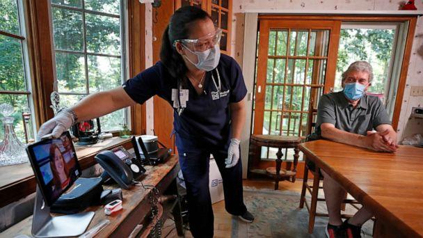 PHOTO: Nurse practitioner Sadie Paez picks up a tablet to set up a telehealth session for William Merry, who is recovering from pneumonia at his home, Thursday, July 9, 2020, in Ipswich, Mass. (Elise Amendola/AP)