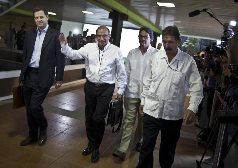 File - In this Nov. 19, 2012 file photo, Humberto de la Calle, second from left, head of Colombia's government peace negotiation team, is accompanied by Sergio Jaramillo, left, and Gustavo Adolfo Bell Lemus, second from right, as they are escorted by a Cuban security official, right, to peace talks with the Revolutionary Armed Forces of Colombia, or FARC, in Havana, Cuba. While the angry rhetoric and bombs continue to fly back home, Colombian rebels and government negotiators in peace talks in the Cuban capital describe an increasingly collegial atmosphere and growing trust between otherwise mortal enemies. (AP Photo/Ramon Espinosa, File)