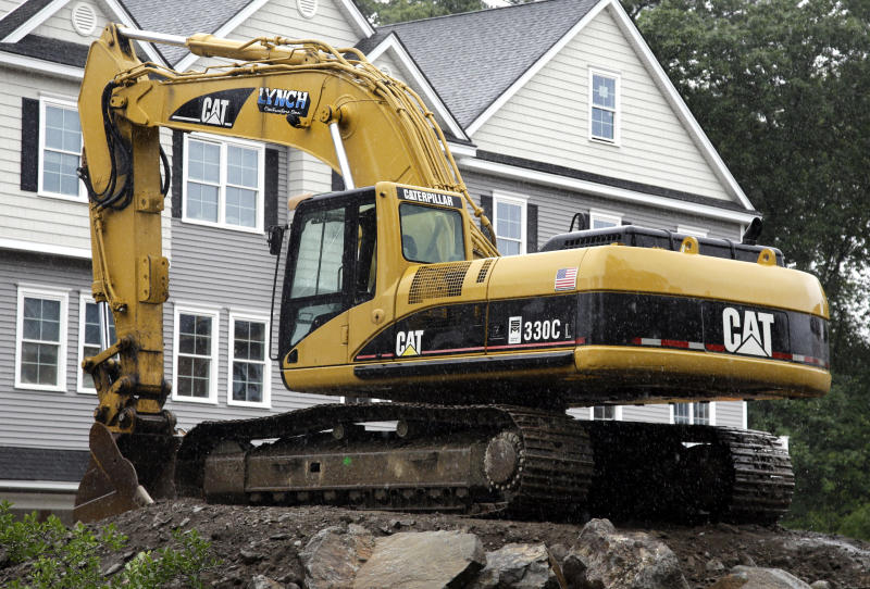 FILE- In this July 24, 2017, file photo, a Caterpillar excavator rests at a housing construction site in North Andover, Mass. Caterpillar Inc. reports earnings Tuesday, Oct. 23, 2018. (AP Photo/Elise Amendola, FIle)