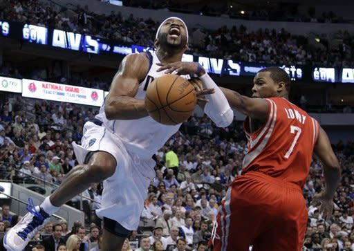 Dallas Mavericks' Vince Carter, left, if fouled by Houston Rockets' Kyle Lowry (7) while going to the basket in the first half of an NBA basketball game on Wednesday, April 18, 2012, in Dallas. (AP Photo/Tony Gutierrez)