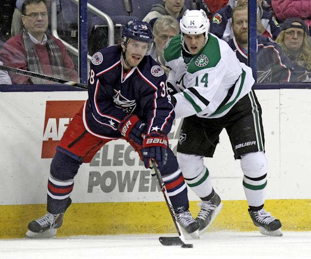 Columbus Blue Jackets' Boone Jenner, left, passes the puck in front of Dallas Stars' Jamie Benn in the first period of an NHL hockey game in Columbus, Ohio, Tuesday, March 4, 2014. (AP Photo/Paul Vernon)
