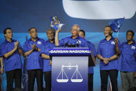 """Then Malaysia's Prime Minister and President of the ruling party coalition """"National Front"""", Najib Razak, center, holds a manifesto booklet during launching event for upcoming general elections in Kuala Lumpur, Malaysia on April 7, 2018. Najib was found guilty Tuesday, July 28, 2020 in his first corruption trial linked to one of the world's biggest financial scandals - the billion-dollar looting of the 1MDB state investment fund. (AP Photo/Vincent Thian)"""