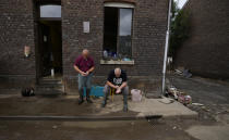 Resident Patrick Martin, right, and a friend in front of their flood damaged home in the La Brouck neighborhood of Trooz, Belgium, Tuesday, July 27, 2021. Patrick Martin and his companion Cindy Lacroix still find it hard to sleep after they feared for their lives during deadly floods nearly two weeks ago, isolated and trapped in the top floor of their house for two days before they were rescued on a small boat by firefighters. (AP Photo/Virginia Mayo)