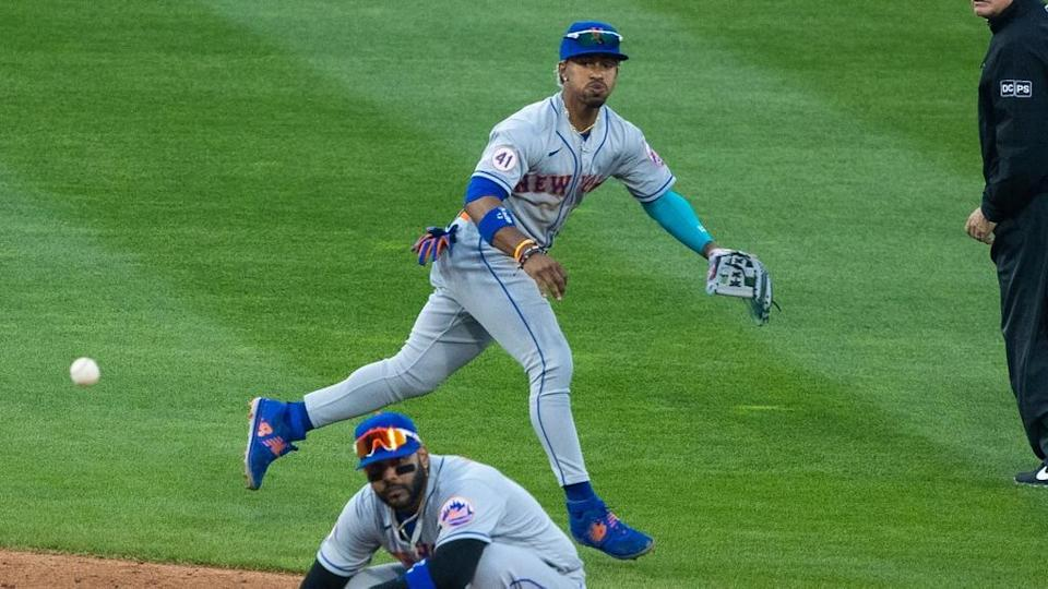 Francisco Lindor Mets goes airborne to throw to first base above Jonathan Villar. Full body
