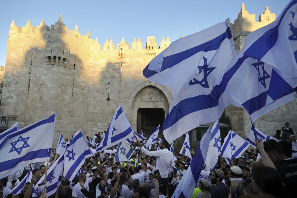 """Jewish ultranationalists wave Israeli flags during the """"Flags March,"""" next to Damascus gate, outside Jerusalem's Old City, Tuesday, June 15, 2021. (AP Photo/Mahmoud Illean)"""