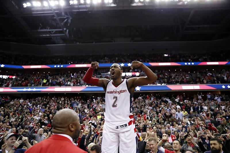 An emotional John Wall roars as he celebrates the Wizards' season-extending Game 6 win. (AP)