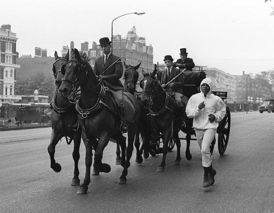 <p>World heavyweight boxing champion Cassius Clay runs alongside a horse-drawn carriage, in Queen's Mews, Knightsbridge, London, May 11, 1966. Clay is in training for his fight against British challenger Henry Cooper on May 21. (AP Photo/Peter Kemp)</p>