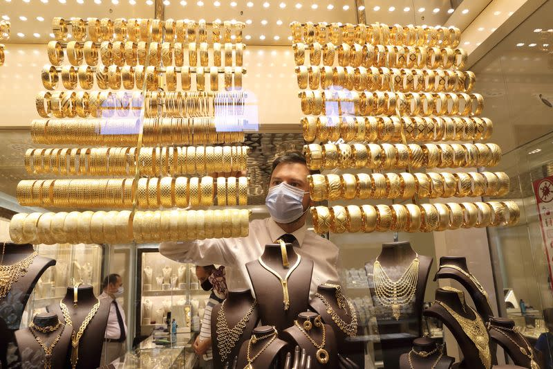 A goldsmith arranges golden bangles at a jewellery shop, in Istanbul