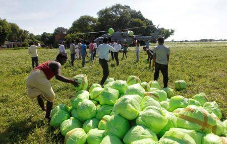People unload relief food material from an Indian Air Force helicopter to be distributed among the flood victims, on the outskirts of Allahabad, India, August 24, 2016. REUTERS/Jitendra Prakash