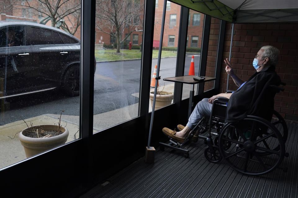 John O'Malley, right, visits with his son during a drive-by visit at The Hebrew Home at Riverdale in New York, Wednesday, Dec. 9, 2020. New dog recruits are helping to expand the nursing home's pet therapy program, giving residents and staff physical comfort while human visitors are still restricted because of the pandemic. (AP Photo/Seth Wenig)