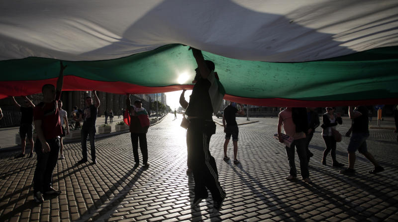 Demonstrators carry a giant Bulgarian flag during a protest against the center-right GERB party in Sofia, Saturday, May 11, 2013. Bulgarian prosecutors have stormed a printing house and seized 350,000 illegally printed ballots just hours before the start of parliamentary elections. Vote-buying and other election fraud concerns have prompted the Organisation for Security and Cooperation in Europe (OSCE) to dispatch its biggest monitoring mission to Bulgaria since 1990 for Sunday's vote. (AP Photo/Valentina Petrova)