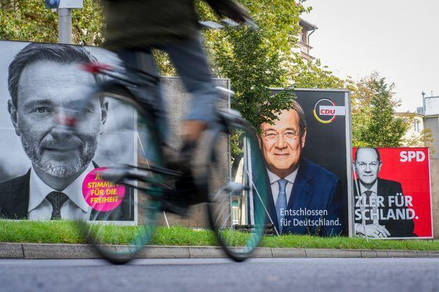 21 September 2021, Berlin: A cyclist rides past large election posters with the chancellor candidates of the SPD with Olaf Scholz (r-l), of the CDU with Armin Laschet and the FDP top candidate Christian Lindner. On 26.09.2021 the German citizens are called to elect a new Bundestag. Photo: Kay Nietfeld/dpa (Photo by Kay Nietfeld/picture alliance via Getty Images) (Photo: picture alliance via Getty Images)