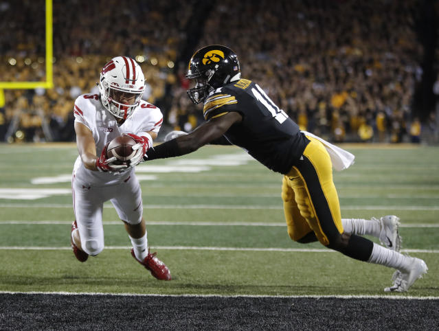 Wisconsin wide receiver Danny Davis, left, dives over the goal line for the touchdown despite defensive efforts by Iowa defensive back Michael Ojemudia, right, during the second half of an NCAA college football game, Saturday, Sept. 22, 2018, in Iowa City. (AP Photo/Matthew Putney)
