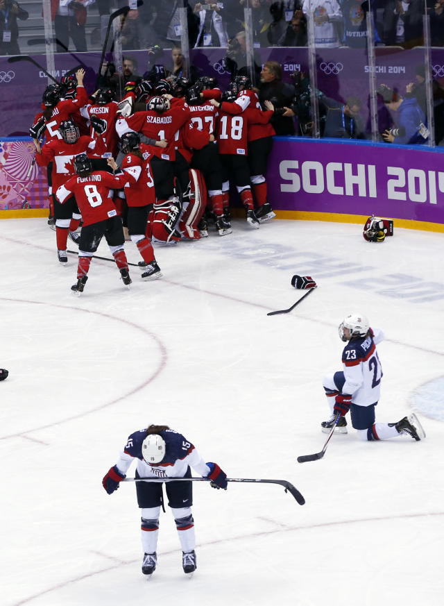Anne Schleper of the United States (15) and Michelle Picard (23) react after the women's gold medal ice hockey game against Canada at the 2014 Winter Olympics, Thursday, Feb. 20, 2014, in Sochi, Russia. (AP Photo/Petr David Josek)