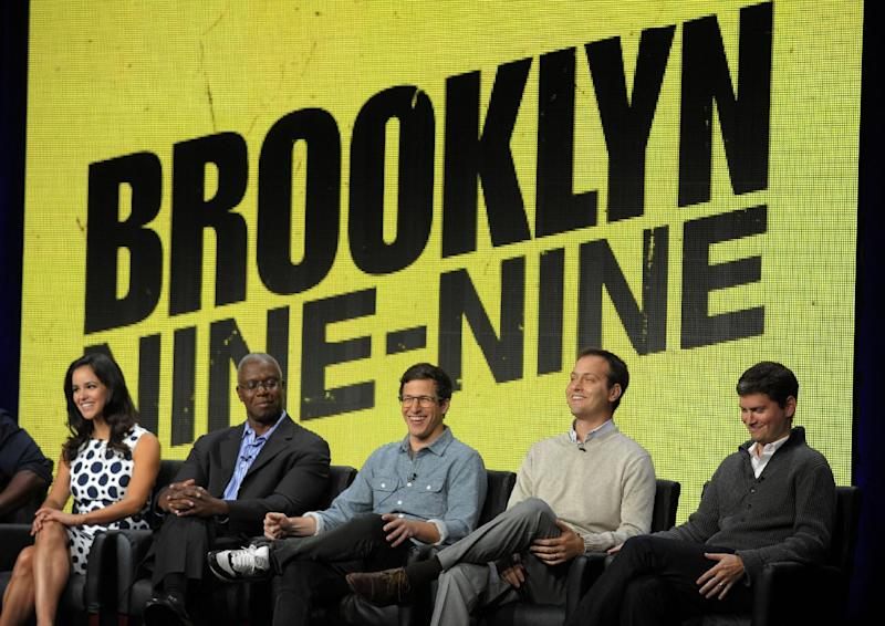 """FILE - In this Aug. 1, 2013 file photo, from left, """"Brooklyn Nine-Nine"""" cast members Melissa Fumero, Andre Braugher and Andy Samberg, and co-creators/executive producers Dan Goor and Michael Schur take part in a panel discussion on the series during the FOX 2013 Summer TCA press tour at the Beverly Hilton Hotel, in Beverly Hills, Calif. Fox says the plum post-Super Bowl slot next February will be filled by two of its comedies. """"New Girl"""" and freshman series """"Brooklyn Nine-Nine"""" will air on Fox after the game that's typically TV's most-watched program and a big promotional platform for other network fare. (Photo by Chris Pizzello/Invision/AP, File)"""