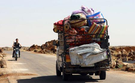 A man rides on a motorbike near a truck loaded with belongings in Deraa countryside, Syria June 22, 2018. REUTERS/Alaa al-Faqir