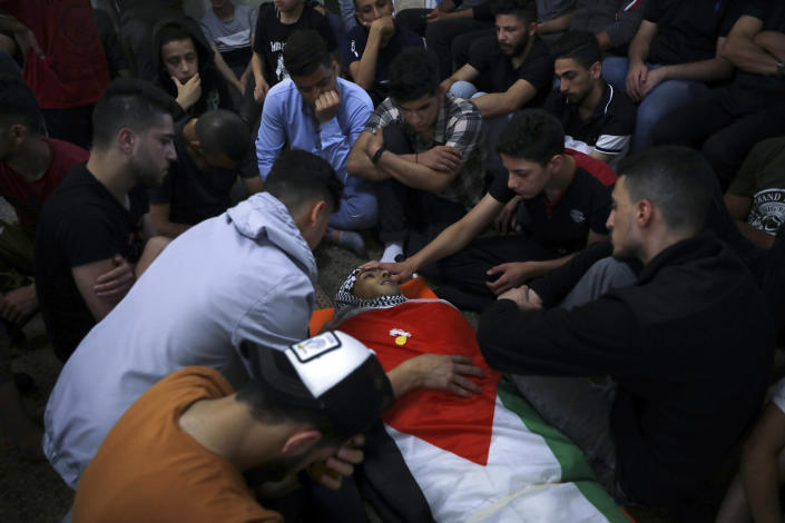 Palestinian mourners gather around the body of Obaida Jawabreh, who was killed in clashes with Israeli forces, during his funeral in the West Bank refugee camp of Al-Arrub, Tuesday, May 18, 2021. (AP Photo/Mahmoud Illean)