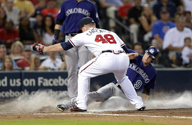 Colorado Rockies second baseman DJ LeMahieu (9) scores on a wild pitch as Atlanta Braves relief pitcher David Carpenter (48) covers the plate in the fourth inning of a baseball game in Atlanta, Monday, July 29, 2013. (AP Photo/John Bazemore)