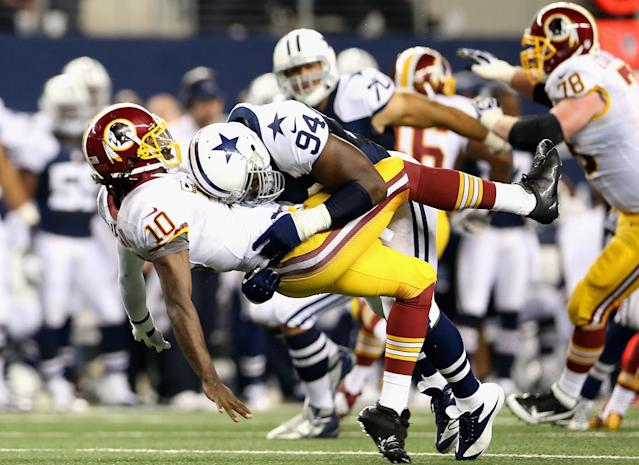 ARLINGTON, TX - NOVEMBER 22: Robert Griffin III #10 of the Washington Redskins is tackled by DeMarcus Ware #94 of the Dallas Cowboys during a Thanksgiving Day game at Cowboys Stadium on November 22, 2012 in Arlington, Texas. (Photo by Ronald Martinez/Getty Images)