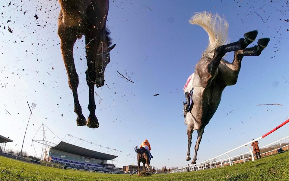 Action as runners clear a fence in the straight during The Close Brothers Handicap Chase at Kempton Park  - PA