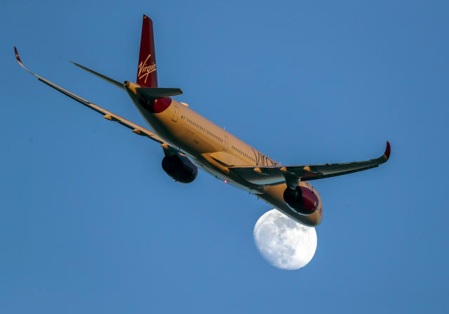 A Virgin Atlantic Airbus A350-1041 with registration G-VLUX passes the moon as it takes off from Heathrow Airport. (Photo by Steve Parsons/PA Images via Getty Images)