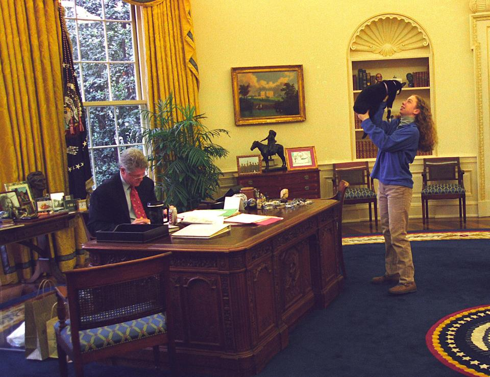 <p>President Bill Clinton works at his desk while First Daughter Chelsea Clinton plays with First Pet Socks the Cat in December 1994. </p>