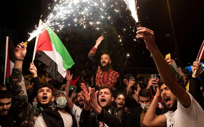 Protestors hold Palestinian flags and shout slogans against Israel during a demonstration in front of Israel Consulate in Istanbul