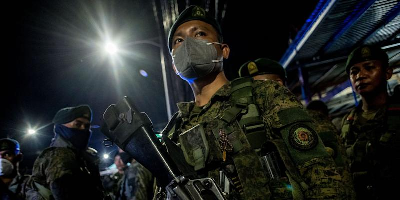Soldiers stay at a checkpoint in the Philippines at midnight in March