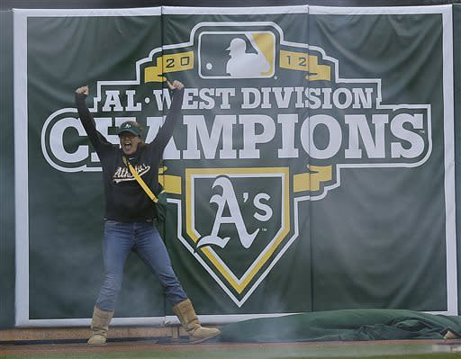 An Oakland Athletics fan cheers as the new Western Divisional banner is unfurled prior to the baseball game against the Seattle Mariners Monday, April 1, 2013, in Oakland, Calif. (AP Photo/Ben Margot)