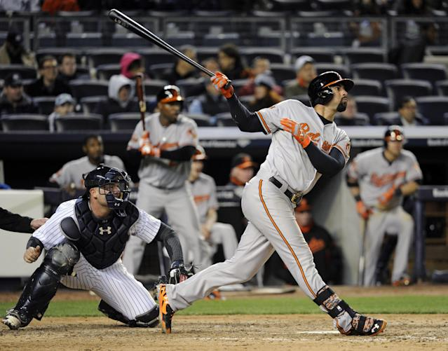 Baltimore Orioles' Nick Markakis follows through on an RBI single as New York Yankees catcher Brian McCann watches during the ninth inning of a baseball game Wednesday, April 9, 2014, at Yankee Stadium in New York. The Orioles won 5-4. (AP Photo/Bill Kostroun)