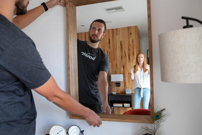 Steven and Kylee Niederhauser co-owners of Haustay straighten a mirror before guest arrive in their vacation rental property in La Quinta, Calif., on Saturday, July 11, 2020.