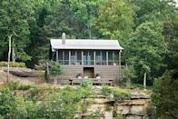 """<p>A former <em>Southern Living</em> editor-in-chief built this <a href=""""https://www.southernliving.com/home-garden/decorating/small-alabama-lake-house?"""" rel=""""nofollow noopener"""" target=""""_blank"""" data-ylk=""""slk:rustic-modern cabin"""" class=""""link rapid-noclick-resp"""">rustic-modern cabin</a> as a lakeside retreat. With a breezy screened porch and open-concept floor plan, there's plenty of space to entertain. Each bedroom features a private bath and walk-in closet.</p> <p>Two bedrooms, two baths</p> <p>1,031, square feet</p> <p>See plan: <a href=""""https://houseplans.southernliving.com/plans/SL1948?index=1&search%5Bbedrooms%5D%5B%5D=2&search%5Bplan%5D=&search%5Butf8%5D=✓"""" rel=""""nofollow noopener"""" target=""""_blank"""" data-ylk=""""slk:New Bunkhouse (SL-1948)"""" class=""""link rapid-noclick-resp"""">New Bunkhouse (SL-1948)</a></p>"""