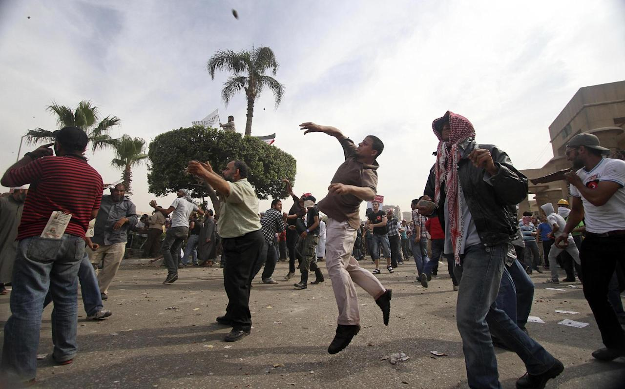 Protesters throw stones during clashes outside the Ministry of Defense in Cairo, Egypt, Friday, May 4, 2012. Egyptian armed forces and protesters clashed in Cairo on Friday, with troops firing water cannons and tear gas at demonstrators who threw stones as they tried to march on the Defense Ministry, a flashpoint for a new cycle of violence only weeks ahead of presidential elections. (AP Photo/Ahmed Gomaa)