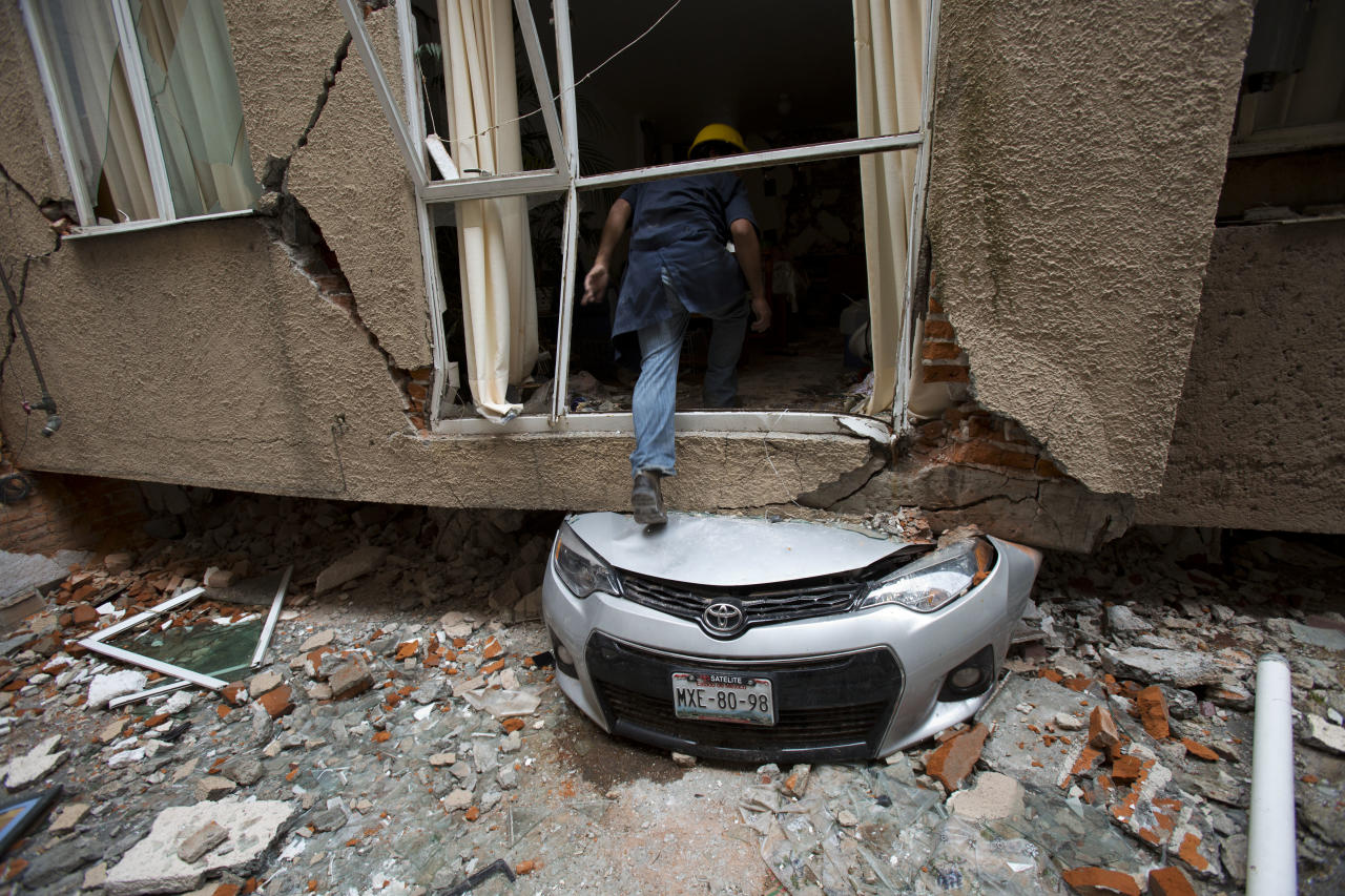 Rodrigo Diaz Mejia climbs over a crushed car into what was a second-story apartment at 517 Tokio street, felled by the earthquake almost one month ago in the Portales Norte neighborhood of Mexico City, Wednesday, Oct. 18, 2017. The 38-year-old mechanic who lives nearby said he ran to help rescue people trapped atop the buildings roofs on the day of the quake, Sept. 19, and has since been making risky trips into the ruptured structures to retrieve valuable possessions for displaced residents. (AP Photo/Rebecca Blackwell)