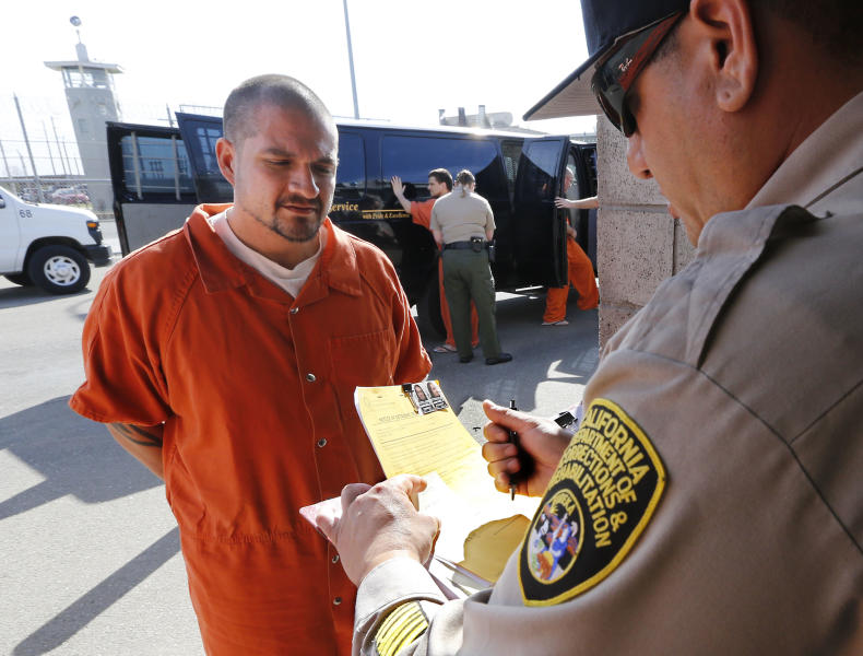 In this photo taken Thursday, Feb. 20, 2014, Derek Martinez, 37, is processed after his arrival at the Deuel Vocational Institution in Tracy Calif. Martinez, a second strike offender from Shasta County, has been serving a life term with the possibility of parole for first degree murder since 2007. California counties are thwarting the state's efforts to comply with a federal court order to reduce it's inmate population by sending state prisons far more convicts than anticipated including a record number of second-strikers. The state is trying to comply with a landmark restructuring of its criminal justice system through a nearly 3-year-old law pushed by Gov. Jerry Brown that keeps lower-level felons in county jails while reserving scarce state prison cells for serious, violent and sexual offenders.(AP Photo/Rich Pedroncelli)