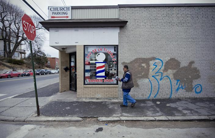 FILE - In this Feb. 15, 2012 file photo a man walks past a barber pole painted in the window of El Rey De La Tijera Barber Shop in Waterbury, Conn. The barber pole, one of the oldest signs that can be seen on storefronts across America, is an increasing source of friction between barbers and beauticians over which businesses get to display the iconic striped poles. (AP Photo/Jessica Hill, File)