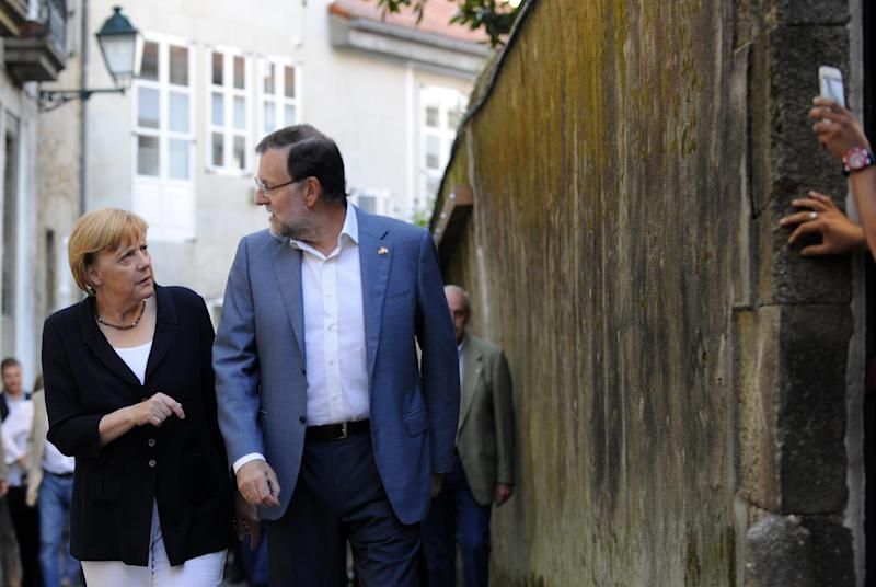 German Chancellor Angela Merkel (L) and Spanish Prime Minister Mariano Rajoy walk in the the old town of Santiago de Compostela before having dinner, on August 24, 2014 (AFP Photo/Miguel Riopa )