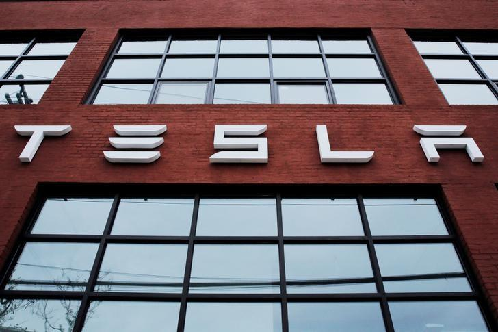 FILE PHOTO: A Tesla logo hangs on a building outside of a Tesla dealership in New York