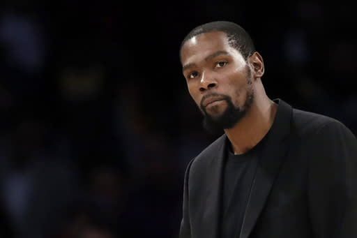 FILE- In this March 10, 2020, file photo, Brooklyn Nets' Kevin Durant watches during the second half of the team's NBA basketball game against the Los Angeles Lakers in Los Angeles. Kevin Durant is finally within weeks of suiting up for the Brooklyn Nets. Sidelined last season while recovering from surgery on his Achilles tendon, he begins training camp this week on a team that can contend for the NBA title if he can be as good as he was before his injury. (AP Photo/Marcio Jose Sanchez, file)