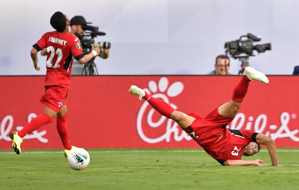 CHARLOTTE, NORTH CAROLINA - JUNE 23: Luis Paradela #23 of Cuba flips as he dives to intercept a pass against Canada during the second half of their Group A 2019 CONCACAF Gold Cup match at Bank of America Stadium on June 23, 2019 in Charlotte, North Carolina. Canada won 7-0. (Photo by Grant Halverson/Getty Images)