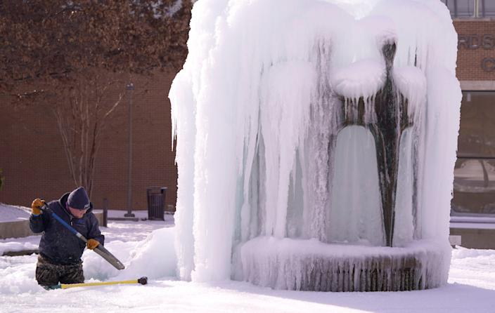 City of Richardson worker Kaleb Love works to clear ice from a water fountain Tuesday, Feb. 16, in Richardson, Texas.