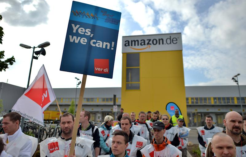 Employees of online retailer Amazon are on strike in front of the company's branch in Leipzig, Germany, Tuesday, May 14, 2013. The ver.di union said it is urging Amazon to adopt wage agreements similar to those governing retail and mail-order workers. The union says those agreements include Christmas bonuses and extra pay for working nights, Sundays and holidays. (AP Photo/dpa, Hendrik Schmidt)