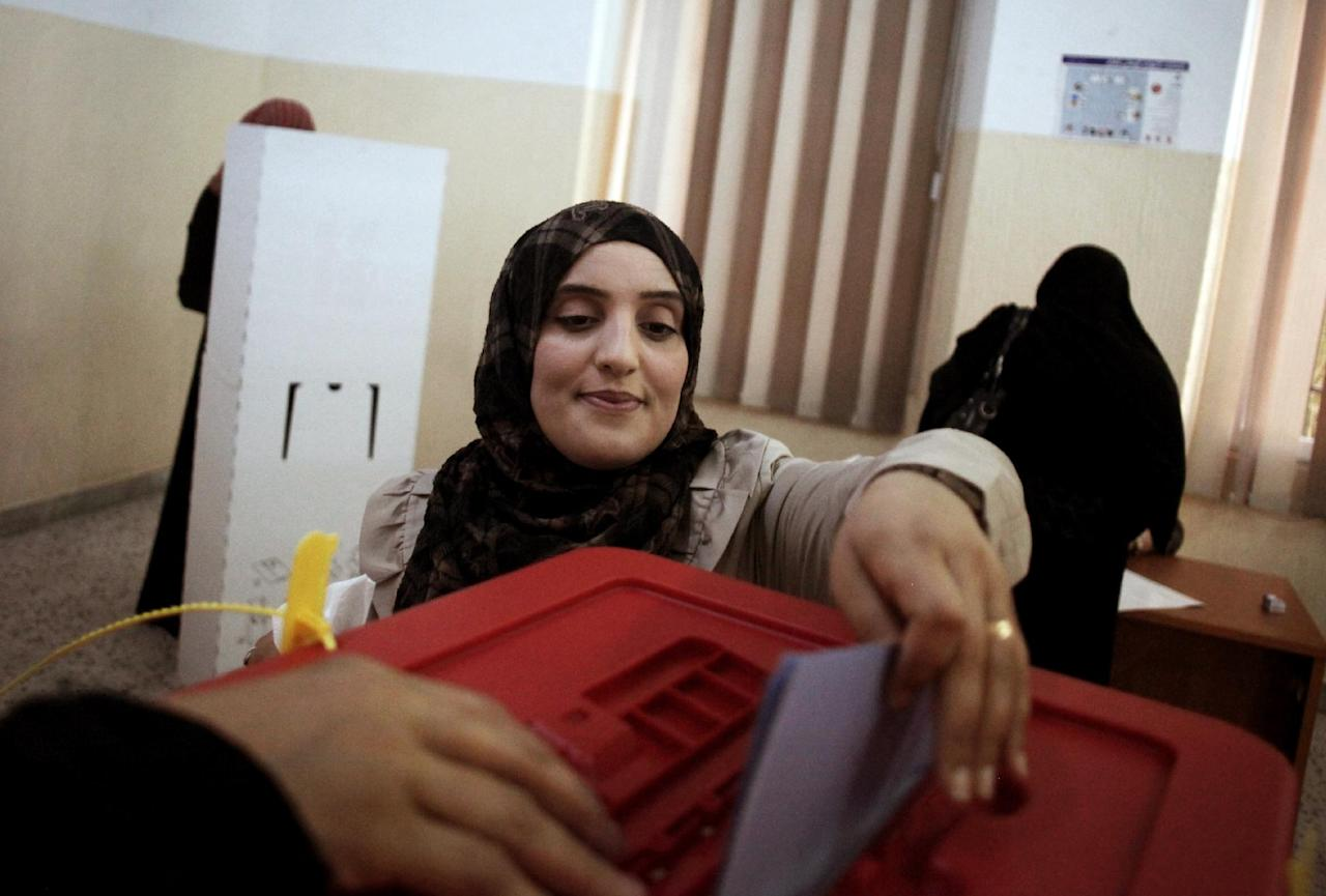 A Libyan woman votes at a polling center in the Old City of Tripoli, Libya, Saturday, July 7, 2012. Jubilant Libyans marked a major step toward democracy after decades of erratic one-man rule, voting Saturday in the first parliamentary election after last yearís overthrow and killing of longtime dictator Moammar Gadhafi. But the joy over the historic vote was tempered by boycott calls, the burning of ballots and other violence in Libyaís restive east.(AP Photo/Manu Brabo)