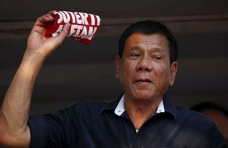 """Presidential candidate Rodrigo """"Digong"""" Duterte holds an election souvenir shirt for his supporters during election campaigning for May 2016 national elections in Malabon, Metro Manila in the Philippines April 27, 2016. REUTERS/Erik De Castro"""