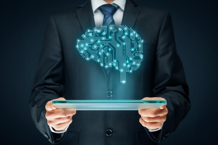 A man in a suit holding a tablet. An illustrated brain made of electrical connections hovers above the tablet, signifying artificial intelligence.
