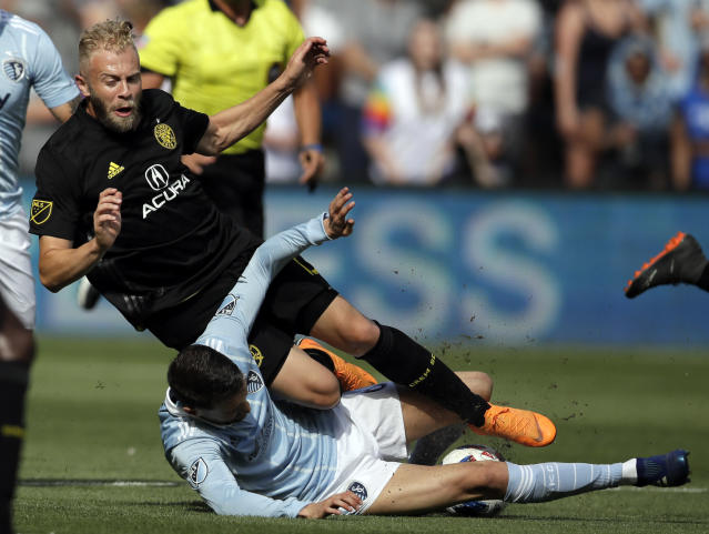 Sporting Kansas City midfielder Ilie Sanchez, bottom, sweeps Columbus Crew forward Mike Grella, top, during the first half of an MLS soccer match in Kansas City, Kan., Sunday, May 27, 2018. (AP Photo/Orlin Wagner)