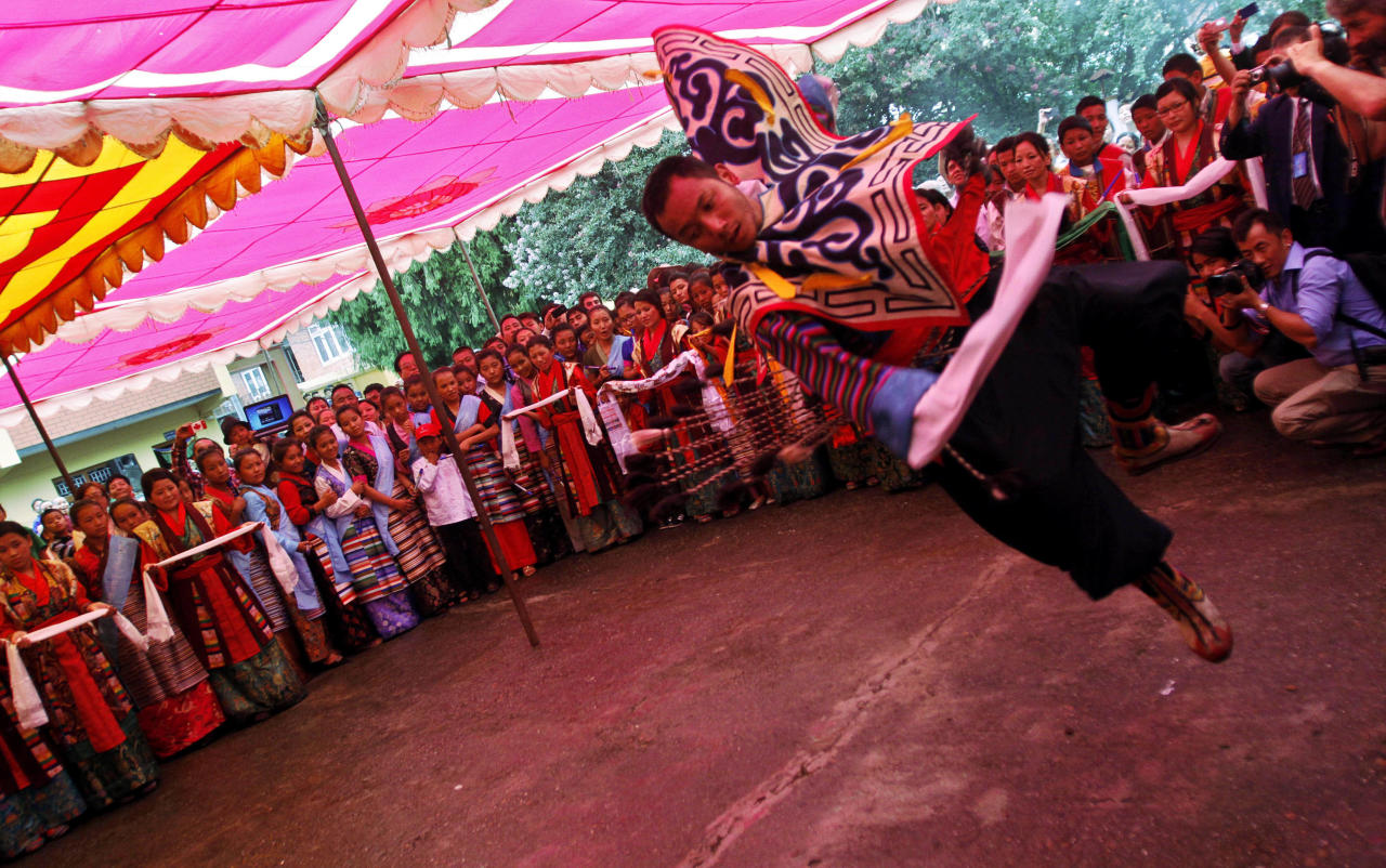 A Tibetan exile performs a traditional dance during celebrations for the birthday of spiritual leader the Dalai Lama at a monastery in Katmandu, Nepal, Friday, July 6, 2012. The Tibetans held celebrations to mark the 77th birthday of the Dalai Lama, who lives in the northern Indian town of Dharmsala after his exile from Tibet during a failed revolt against Chinese rule. (AP Photo/Binod Joshi)
