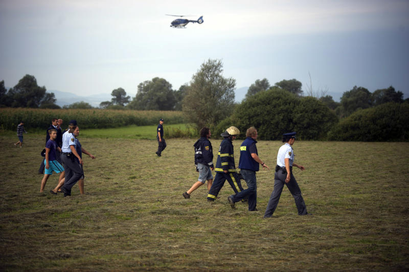 Rescuers survey the site of hot air balloon crash near Ljubljana, Slovenia, Thursday, Aug. 23, 2012. A hot air balloon carrying 32 people crashed, leaving four people dead and 28 injured, authorities confirmed. (AP Photo/Matej Leskovsek)