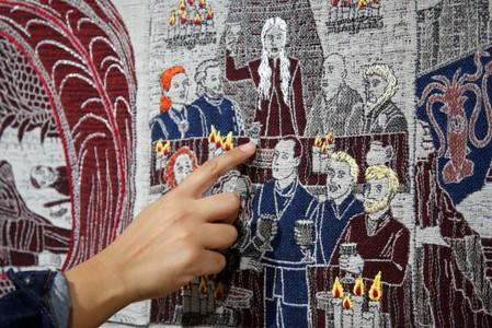 A visitor points at the Starbucks cup of the Game of Thrones Tapestry in Bayeux